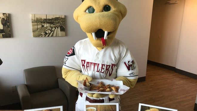 Wisconsin Timber Rattlers mascot, Fang, holds this year's Timber Rattlers Fan's Choice Food Fight winner, Rattler Bites.