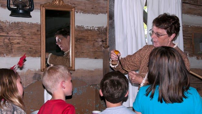 Volunteer Kay Hallett teaches students about how men had to shave their faces in the 1860s during R.C. Waters third graders annual visit to the Oak Harbor log cabin in May 2016.