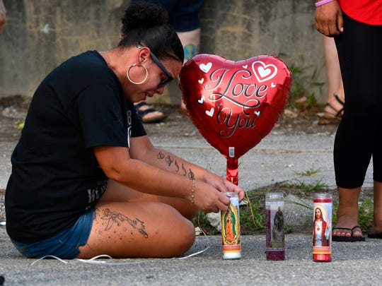 Yolanda Shaw ties a balloon to a candle at the site where her sister, Ruby Mercado, was found murdered. (John A. Pavoncello photo)