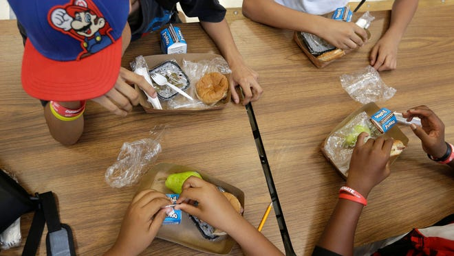 Students at the Maurice J. Tobin K-8 School in Boston's Roxbury neighborhood eat free lunches consisting of a sandwich with meat, a vegetable dish, a piece of fruit and milk on Sept. 4, 2013.