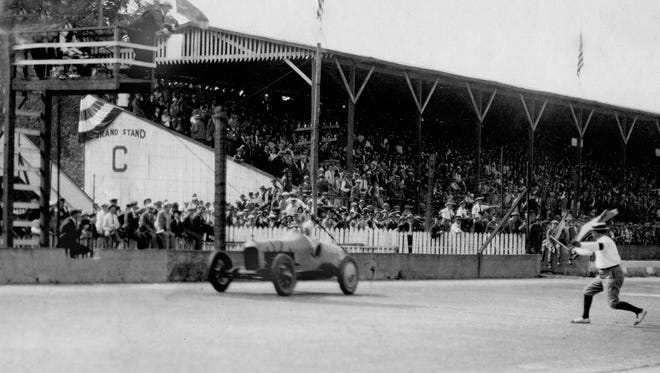 -Pete DePaolo shown getting a flag driving his #12 Duesenberg.