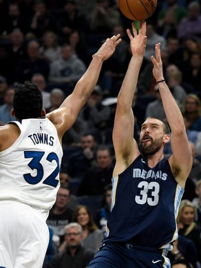 Memphis Grizzlies' Marc Gasol (33), of Spain, shoots against Minnesota Timberwolves' Karl-Anthony Towns (32) during the fourth quarter of an NBA basketball game on Monday, March 26, 2018, in Minneapolis. The Grizzlies won 101-93. (AP Photo/Hannah Foslien)