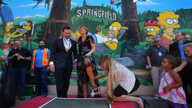 """Actor Yeardley Smith, center, has her shoe wiped off after making her footprints in cement during the unveiling of the new """"The Simpsons"""" mural in Springfield, Ore., Monday, Aug. 25, 2014."""