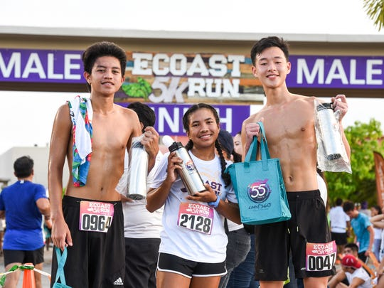 Participants, form left, Jordan Hattori, Sheila Dumaraog and Steven Leung, show their flask containers they received after taking part in the 2017 eCoast 5K Run & Family Fair, hosted by Coast360, at the financial institution's Maite branch on Saturday. Sept. 23, 2017.
