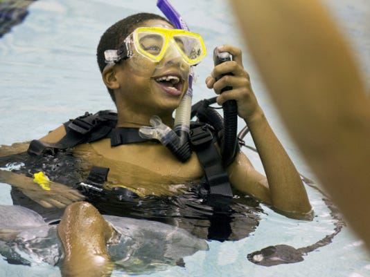 Tymere Forry, 12, of York laughs when the instructor tells him to inflate the part of his scuba gear that lifts him in the water during a Discovery Scuba class at the YMCA in York on Sunday afternoon.