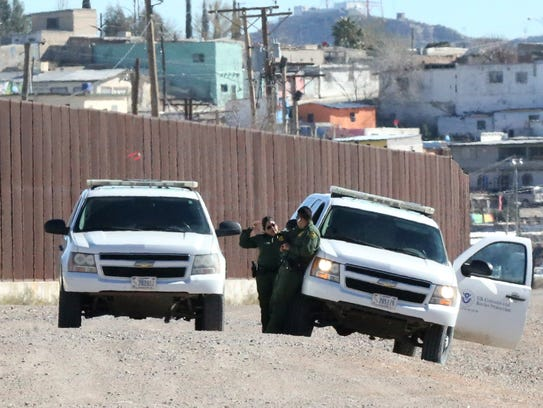 U.S. Border Patrol agents stand next to their vehicles