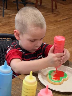 Dean Harte, 5, decorates his heart-shaped sugar cookie with Christmas colors in red and green.