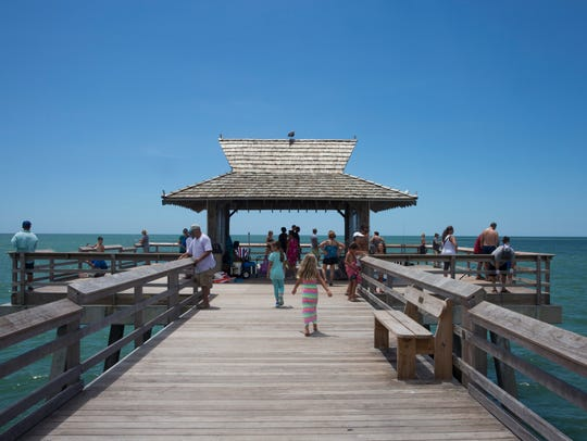 Tourists and locals take in the Gulf of Mexico from