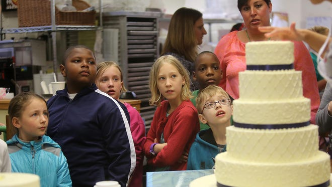 Fourth-grade students from Hyde Park School check out a cake being built during a tour of The BonBonerie bakery in O'Bryonville. The students were part of a business class funded through a Straight A grant.
