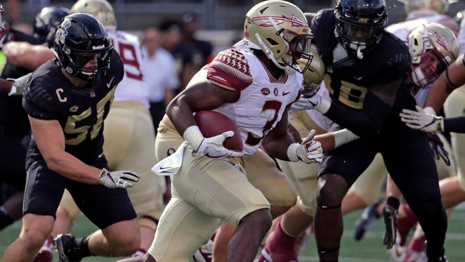 Florida State's Cam Akers (3) runs past Wake Forest's Grant Dawson (50) in the first half of an NCAA college football game in Winston-Salem, N.C., Saturday, Sept. 30, 2017. (AP Photo/Chuck Burton)
