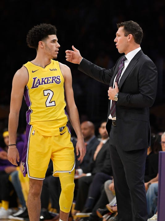 Los Angeles Lakers guard Lonzo Ball, left, talks with coach Luke Walton during the first half of an NBA basketball game against the Los Angeles Clippers, Thursday, Oct. 19, 2017, in Los Angeles. (AP Photo/Mark J. Terrill)