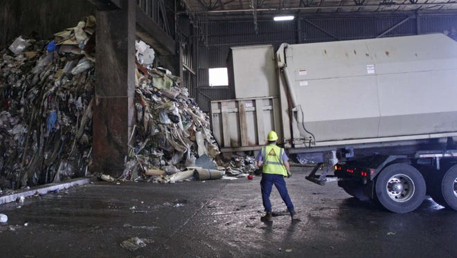 A driver prepares his trailer to dump a load of garbage on the tipping floor at the Covanta Energy facility in 2012.