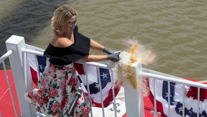 Marissa Applegate smashes a bottle of Maker's Mark bourbon against a railing of the American Duchess riverboat to christen it on Aug. 14, 2017.