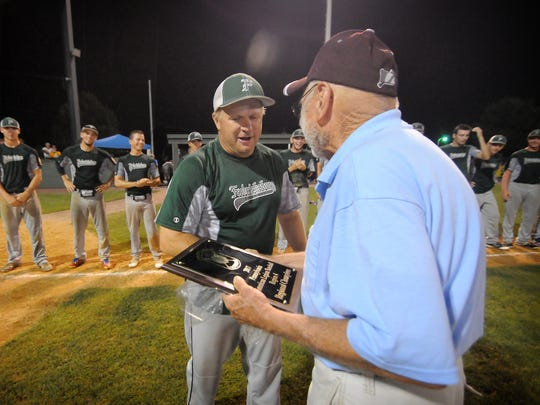 Fredericksburg manager Tim Schaeffer accepts the Region 4 championship trophy after his team topped Pleasureville 10-4 in the title game at Earl Wenger Field Thursday night.