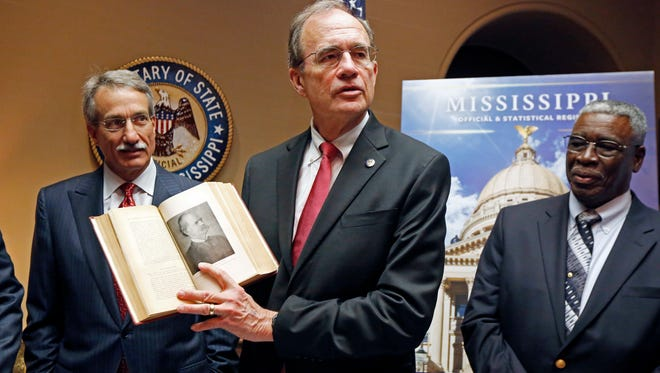 """Secretary of State Delbert Hosemann shows off a copy of a 1917 centennial edition of the Official and Statistical Register of the State of Mississippi, in front of the blowup cover of the bicentennial """"Blue Book"""" released Tuesday at the Capitol in Jackson."""