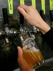 Jennifer Gilmartin of Shrewsbury, operations manager, pours an XPA, a West Coast-style pale ale, at the Asbury Park Brewery in Asbury Park, NJ Wednesday February 15, 2017.