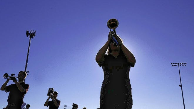 New Albany High School senior Ella Wielinski and others perform Aug. 19 during band practice at the high school stadium. The COVID-19 coronavirus pandemic has caused several changes to the band's schedule and procedures this summer.
