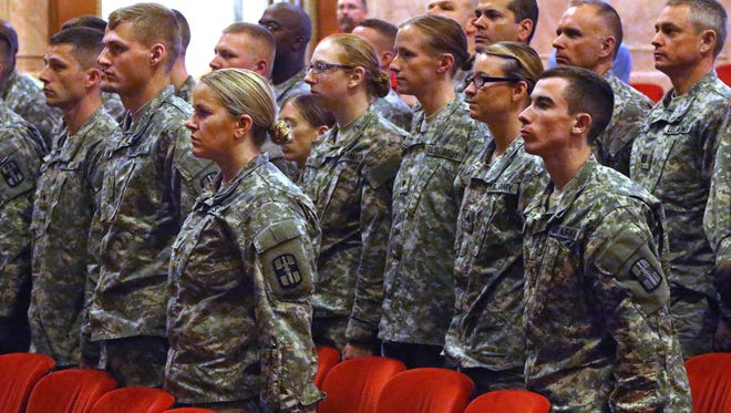 Members of the U.S. Army Reserves 55th Combat Operational Stress Control (medical) detachment stationed at Fort Benjamin Harrison in Lawrence, stand at attention during their deployment ceremony on Saturday, August 2, 2014 at the Indiana War Memorial in Indianapolis. The unit will be providing basic psychological and wellness assistance for deploying and returning soldiers and civilians in Kuwait in support of Operation Enduring Freedom.