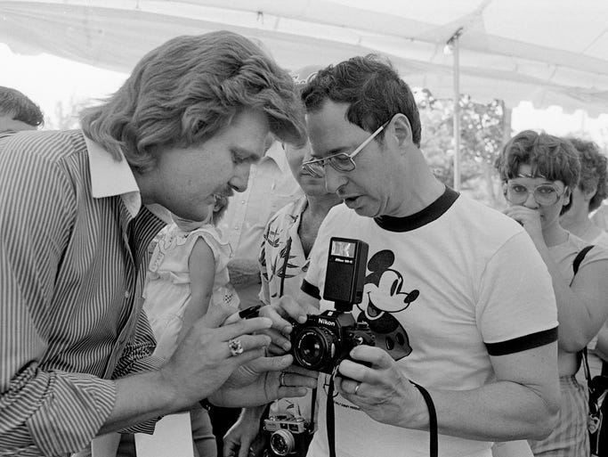 Ricky Skaggs, left, helps a member of his fan club with his camera as he signs autographs for them during his private picnic and show June 6, 1984 for them during Fan Fair.