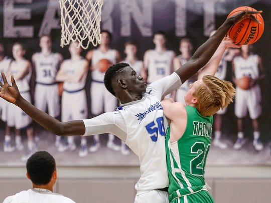 Hamilton Southeastern Royals center Mabor Majak (50) blocks a shot by  New Castle Trojans forward Andrew Froedge (20) on Tuesday, Feb. 7, 2017.