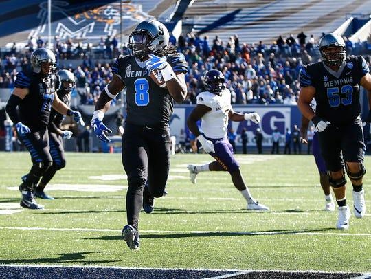 Memphis running back Darrell Henderson (middle) runs