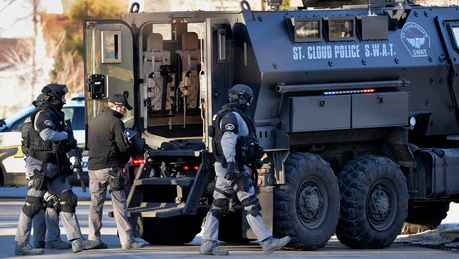St. Cloud Police Department S.W.A.T. team members arrive on the scene of a standoff Tuesday afternoon at a home on the southeast corner of the intersection of 19th Avenue North and Third Street.