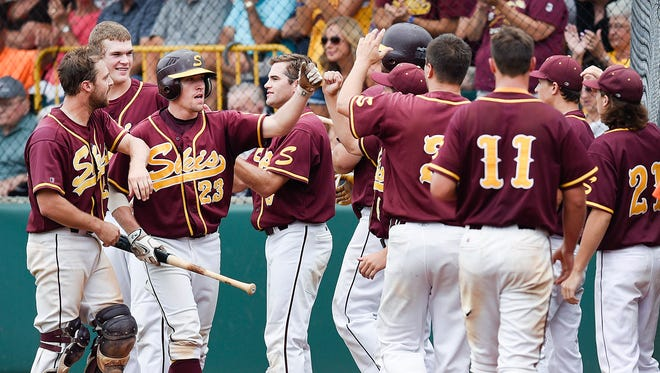 Sobieski's Josh Wenzel, 23, is met by teammates after scoring against  Raymond in the third inning during the 2016 Class C State amateur baseball championship game in Dassel.
