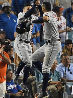 Jose Altuve and Carlos Correa celebrate back-to-back home runs in the 10th inning.