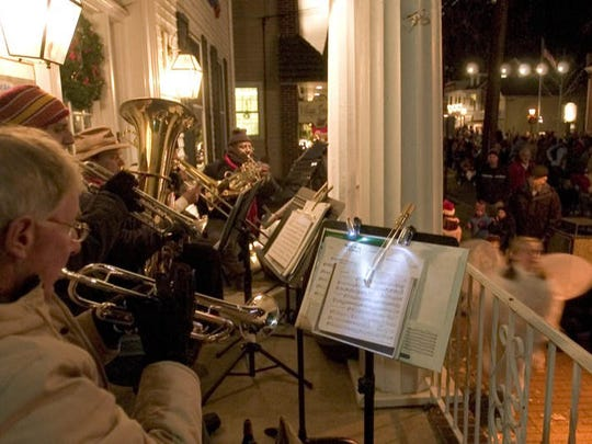 Night strollers enjoy the holiday sounds of The Brass Cosort at a past Dickens Festival in Medford.
