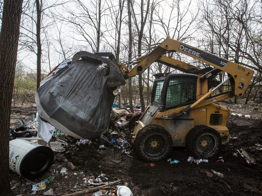 A tent is removed by Louisville Metro Sanitation workers from a homeless camp in Butchertown. March 9, 2018.