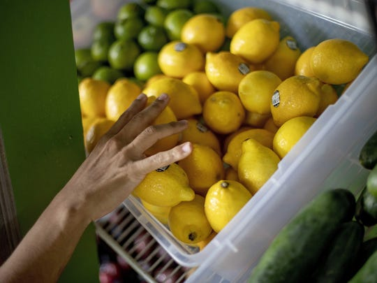 FILE - In this Aug. 21, 2019, file photo a worker stocks a produce stand at a metro station in Atlanta. Throwing away food is throwing away money. And with most wasted food winding up in landfills, it's not great for the environment, either. (AP Photo/David Goldman, File)