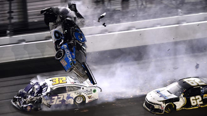 Denny Hamlin, driver of the #11 FedEx Express Toyota, wins over Ryan Blaney, driver of the #12 Menards/Peak Ford, as Ryan Newman, driver of the #6 Koch Industries Ford, crashes and flips behind them during the NASCAR Cup Series 62nd Annual Daytona 500 at Daytona International Speedway on Feb. 17, 2020 in Daytona Beach, Fla.