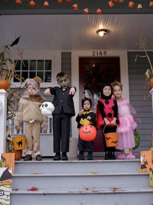 Five children standing on porch, wearing Halloween costumes, portrait