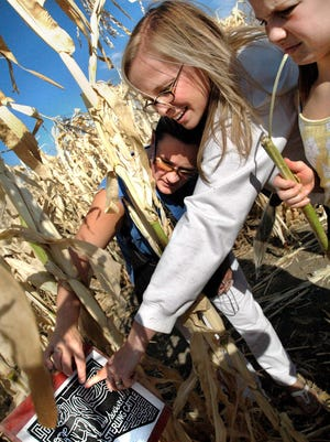Colleen Dabler, left, along with her friend Marni Napierala, center, and Napierala's daughter Rennie, 8, look at the map trying to decide where to go in the Applestem Corn Maze (formerly Sterling Cattle). Check out all the mazes around the state this fall.