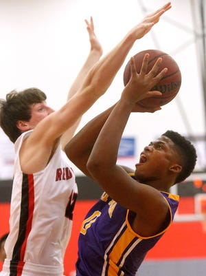 Smyrna's Nick Okeke (0) goes up for a basket as he is guarded by Stewarts Creeks' Daniel Freeman (12) during the game Friday, Feb. 12, 2016, at Stewarts Creek.