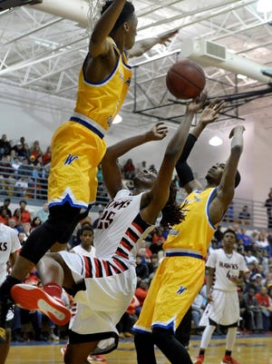 Fayette-Ware's Mikkel Norment (l) and Tyran Gilcrease (r) defend South Side's Geordan Reed (c) during their game Monday.