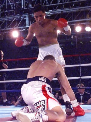 In this June 13, 1998 Oscar De La Hoya stands over his French opponent Patrick Charpentier after knocking him to the canvas in the third round at the Sun Bowl Stadium. De La Hoya was cited for a DUI and released to his manager.