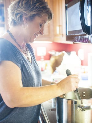 Wendy Newman slowly brings sugar to a boil before adding peanut butter.