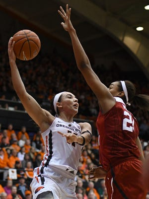 Oregon State guard Gabriella Hanson (11) makes a pass around Stanford forward Erica McCall (24) during the first half of an NCAA college basketball game Friday, Feb. 24, 2017, in Corvallis, Ore.