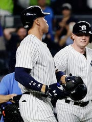 New York Yankees' Aaron Judge reacts after he is hit in the mouth by a helmet he had picked up during Thursday's walk-off celebration against the Tampa Bay Rays on Thursday, July 27, 2017, in New York. The Yankees won 6-5. Judge broke part of a tooth.