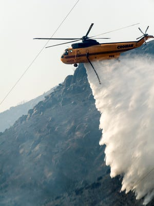 A helicopter drops water as fire fighters from the U.S. Forest Service and Tulare County work the Pier fire on Wednesday, Aug. 30, 2017. There is no containment and it has consumed about 4,655 acres since it was reported about 2:30 a.m. Tuesday.
