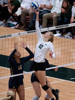 Michigan State's Rachel Minarick, right, hits the ball over the net as Michigan's Kiara Shannon looks on during the second game of the volleyball match on Wednesday, Oct. 18, 2017, at the Jenison Field House in East Lansing.