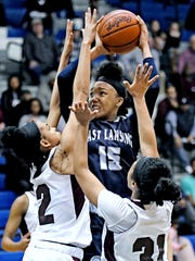 East Lansing's Jaida Hampton, center, shoots as Kalamazoo