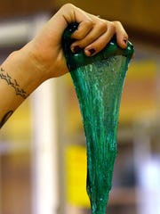 An employee demonstrates the stretchiness of slime for patrons during a slime workshop on Tuesday, April 17, 2018, at Impression 5 Science Center in Lansing. Impression 5 has recovered after a former employee embezzled $162,000 during the 1990s by stealing cash from the slime workshop lock box.