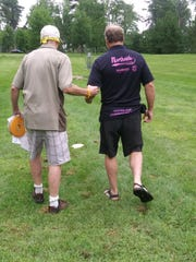Disc golfers Tim Mackey (left) and Rick Rentz walk during a round at Calvary Hill Park. Mackey will be the lead director for blind disc golf as part of the National Veterans Golden Age Games from Aug. 3-8 in Albuquerque, New Mexico.