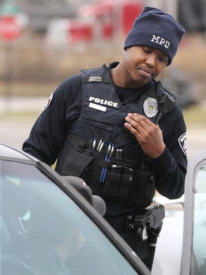 Marion police officer Dwayne Redrick stops a driver displaying a expired license plate while patrolling with department field training officer Norm Roderman on Thursday, Dec. 18, 2014. Redrick, 22, comes from a law enforcement family from the Cleveland area. James Miller/The Marion Star