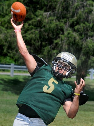 "Alex Marinelli, the quarterback for the Franklin D. Roosevelt High School football team, throws a pass during a recent practice in Hyde Park. Taped on his helmet are the words, ""One Last Time."" Alex is the son of Glenn Marinelli, who died May 30 at the age of 56 after battling cancer since July 2011."