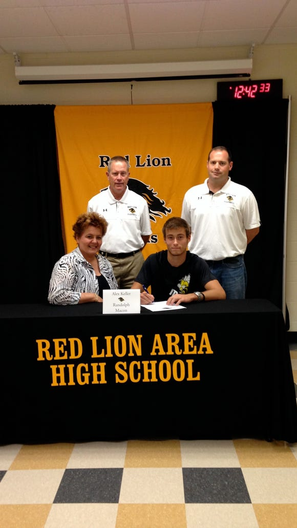 Alex Keller seated next to his mom, Denise Keller, signs his letter of intent to play football at Randolph-Macon College. Standing behind Keller are Red Lion athletic director Arnie Fritzius and football coach Jesse Shay.