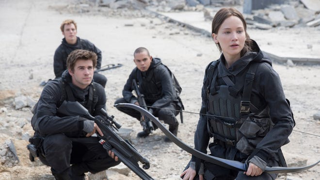 """This photo provided by Lionsgate shows, Liam Hemsworth, left, as Gale Hawthorne, Sam Clafin, back left, as Finnick Odair, Evan Ross, back right, as Messalia, and Jennifer Lawrence, right, as Katniss Everdeen, in the film, """"The Hunger Games: Mockingjay - Part 2.""""  The movie opened in U.S. theaters on Nov. 20, 2015. (Murray Close/Lionsgate via AP)"""