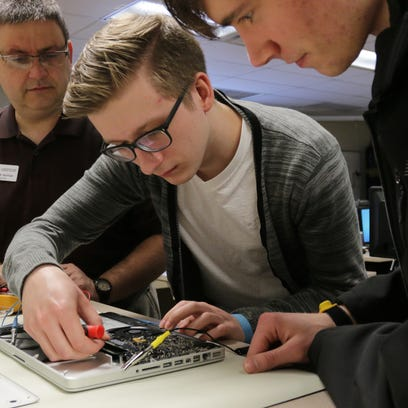 IT instructor Paul Benfield, left, observes while Landon Boettcher of Two Rivers, middle, and Brandon Spindler, 19, of Kiel, right, listen during a network support class Thursday at Lakeshore Technical College in Cleveland.
